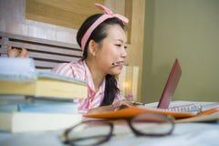 书呆子玻璃的在家学习卧室的年轻逗人喜爱和愉快的讨厌的亚裔韩国学生少年女孩和头发丝带坐  免版税图库摄影