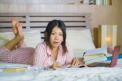 书呆子玻璃的在家学习卧室的年轻逗人喜爱和愉快的讨厌的亚裔韩国学生少年女孩和头发丝带坐  图库摄影