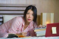 书呆子玻璃的在家学习卧室的年轻逗人喜爱和愉快的讨厌的亚裔韩国学生少年女孩和头发丝带坐  免版税库存照片