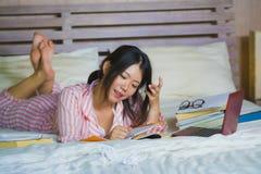 书呆子玻璃的在家学习卧室的年轻逗人喜爱和愉快的讨厌的亚裔韩国学生少年女孩和头发丝带坐  库存图片