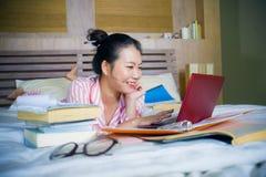 书呆子玻璃的在家学习卧室的年轻逗人喜爱和愉快的讨厌的亚裔韩国学生少年女孩和头发丝带坐  免版税库存图片