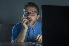 书呆子玻璃的好色被激起的色情上瘾者人在网上观看性电影的夜间在看堕落者的手提电脑和 免版税图库摄影