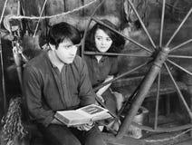读书和一个少妇的年轻人坐在他旁边(所有人被描述不更长生存,并且庄园不存在 S 免版税图库摄影