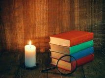 书和一个白色蜡烛在一张木桌上 读由烛光 葡萄酒构成 库存图片
