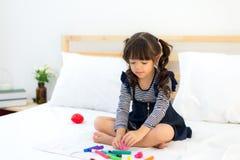 读书和使用与她的玩具玩具熊的滑稽的愉快的小孩女孩在床上 孩子戏剧在家 白色托儿所 免版税库存照片