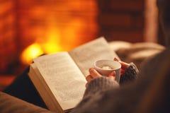 书和咖啡在女孩的手上在平衡的冬天近 免版税图库摄影