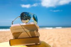 书和太阳镜在海滩 免版税图库摄影