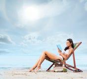 读书和放松在海滩的一名年轻深色的妇女 库存图片