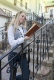 读书和放松想法 户外肉欲的白种人白肤金发的妇女阅读书画象在城市 库存照片