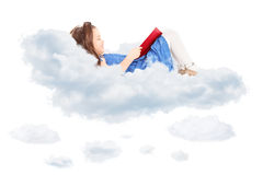 读书和放置在云彩的逗人喜爱的小女孩 免版税库存照片
