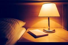 书和灯在床头柜上在旅馆客房 图库摄影
