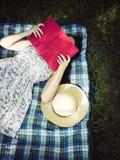 读书和盖面孔的妇女外面 免版税图库摄影