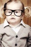 戴书和眼镜的年轻聪明的女孩 免版税库存照片