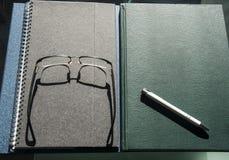 书和笔记本堆与笔和玻璃 库存照片