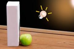 书和绿色苹果在黑板背景 免版税库存图片