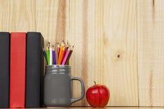 书和铅笔在一个架子刺激用苹果 免版税库存图片
