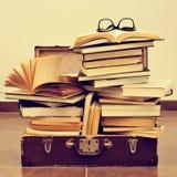 书和镜片在一个老手提箱,有一个减速火箭的作用的 库存图片