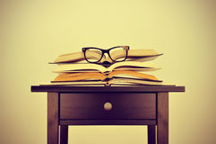 书和镜片在一张书桌上,有一个减速火箭的作用的 免版税库存照片