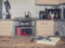 书和玻璃在桌上在厨房里 图库摄影