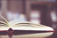 书在一个木桌和书架安置在图书馆 免版税库存照片