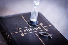 书在皮革黑捆绑的圣经特写镜头的图象与有基督徒鱼象的在灰色模糊的背景的拉链和滴漏 库存图片