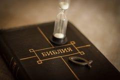 书在皮革黑捆绑的圣经特写镜头的图象与有基督徒鱼象的在灰色模糊的背景的拉链和滴漏 免版税图库摄影