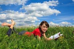 书女孩室外读取 免版税库存图片