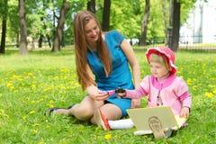 书女孩母亲公园读取 免版税库存照片