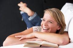 书女孩纵向少年读取的工作室 免版税库存图片