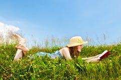 书女孩草甸读取年轻人 免版税图库摄影
