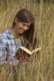 书女孩草纵向读取 免版税图库摄影