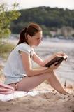 书女孩读取河沿年轻人 免版税库存照片