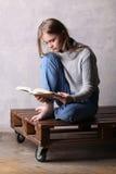 书女孩读取开会 灰色背景 免版税库存照片