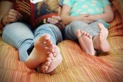 读书妈妈和女儿的脚 库存照片