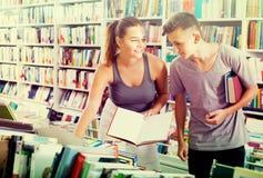 书店的女孩和男孩少年 免版税库存照片