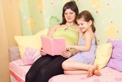 书怀孕女儿的妈咪读 图库摄影