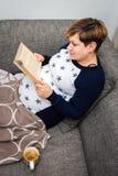 书怀孕的读取妇女 免版税库存图片