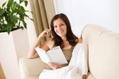 书愉快的读的沙发妇女年轻人 库存图片