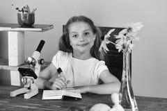 书房和秀丽概念 她的服务台的女小学生 免版税库存图片