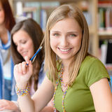 书房的微笑的少年学员女孩 免版税库存照片