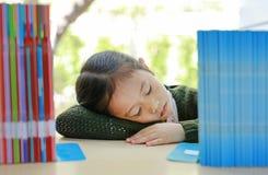 书架的睡觉的亚裔小孩女孩在图书馆 r 免版税库存照片