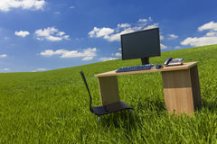书桌和计算机在绿色领域与蓝天 免版税库存照片