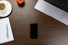 书桌在有一个笔记本在苹果旁边和杯子的办公室  库存图片