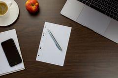 书桌在有一个笔记本在苹果旁边和杯子的办公室c 免版税库存图片