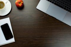 书桌在有一个笔记本在苹果旁边和杯子的办公室c 免版税图库摄影