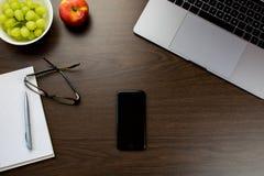 书桌在有一个笔记本的办公室在葡萄和苹果旁边, 库存照片