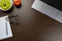 书桌在有一个笔记本的办公室在葡萄和苹果旁边, 图库摄影