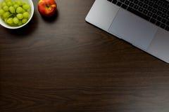 书桌在有一个笔记本的办公室在葡萄和苹果旁边, 免版税图库摄影