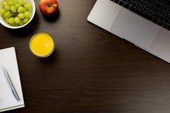 书桌在有一个笔记本的在葡萄旁边,苹果办公室和 图库摄影