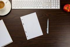 书桌在有笔记的办公室和笔,在杯子o旁边的一个键盘 图库摄影